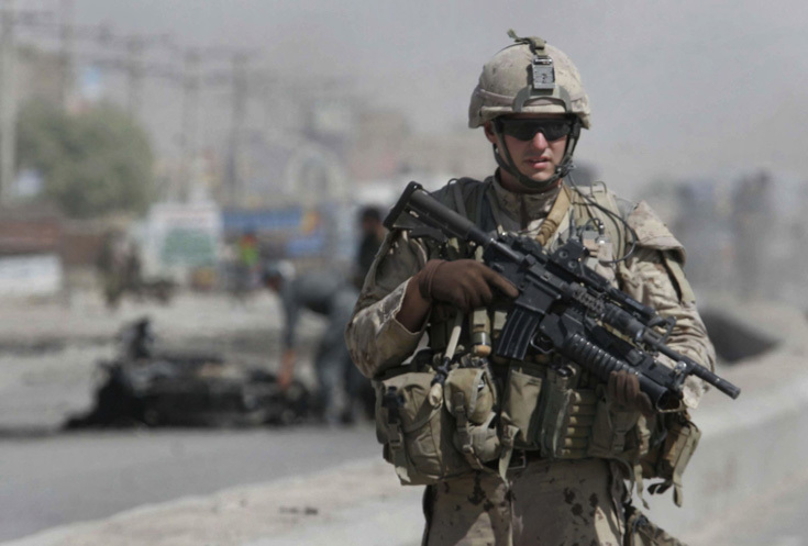 A Canadian soldier with the International Security Assistance Force (ISAF) stands guard at the side of a suicide attack in the city of Kandahar, south of Kabul, Afghanistan on Thursday, Sept. 11, 2008. A suicide bomber attacked a private security company's convoy in Afghanistan's second largest city Thursday, killing two civilians and wounding four other people, a police officer said. (AP Photo/Allauddin Khan)